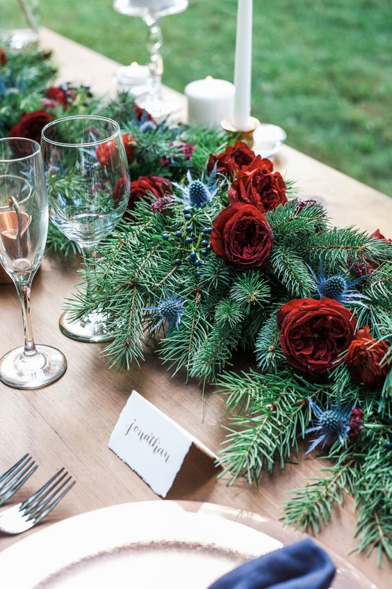 a gorgeous wedding table runner of evergreens, red roses and thistles is a fresh take on classics for a winter wedding