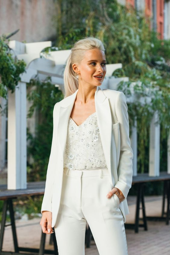 a refined bridal tuxedo in ivory, a lace and embellished top plus floral earrings for a beautiful and chic reception look