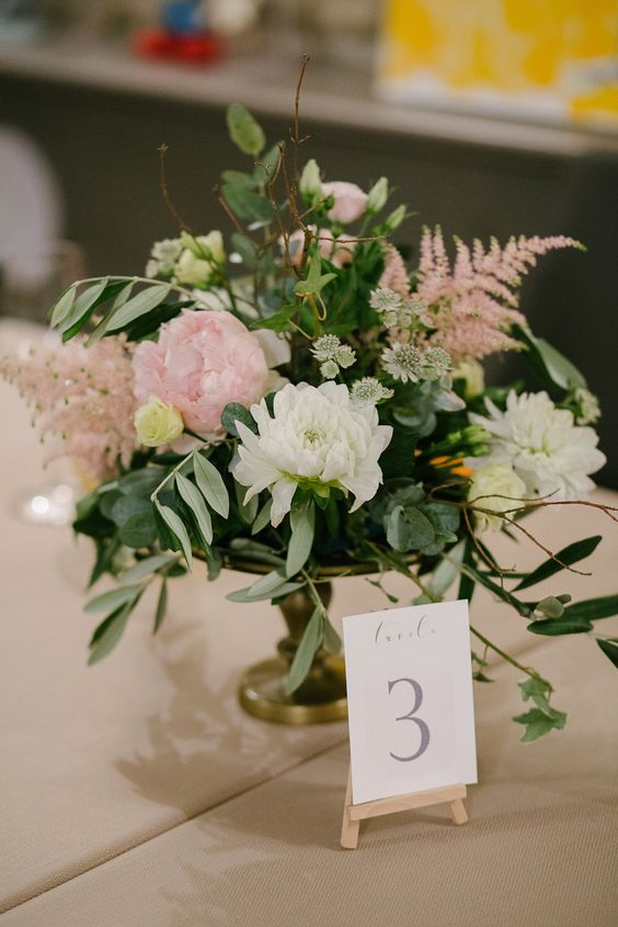 a refined wedding centerpiece with white and pink blooms, greenery, branches and pink astilbe is a gorgeous idea for many weddings