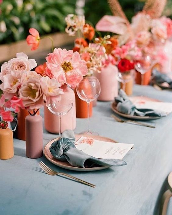 an arrangement of pink, mauve, orange and terracotta vases with blush and coral peonies as a wedding table runner