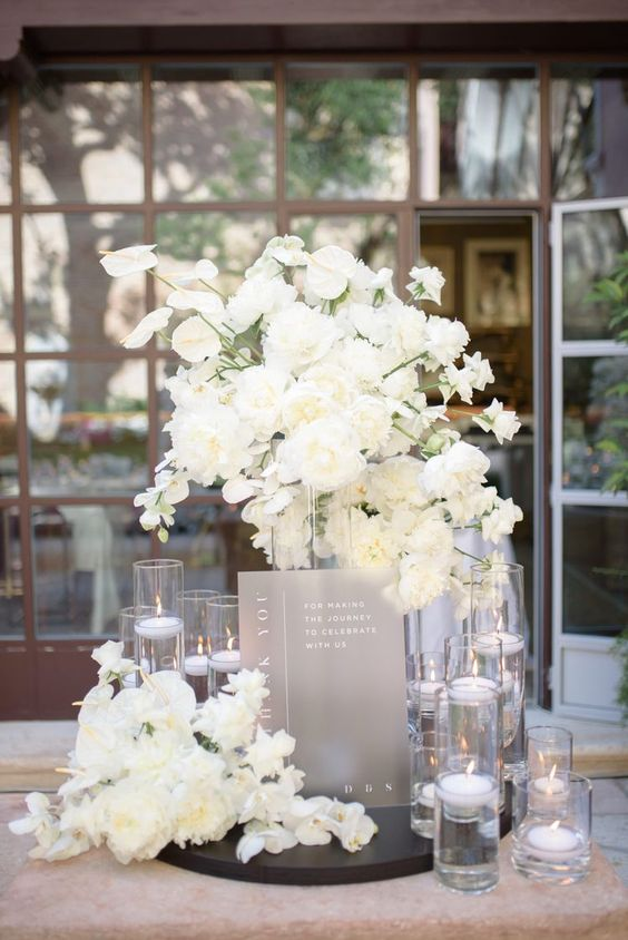 31 modern glam wedding decor with white blooms, floating candles and a grey program is chic and refined