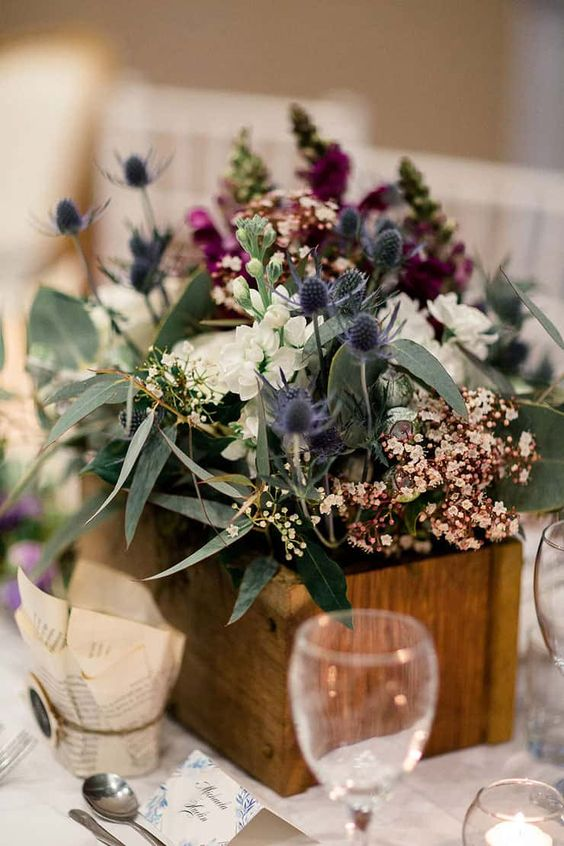 a pretty and chic wedding centerpiece of a wooden box, white, purple and blush blooms, thistles and greenery is amazing