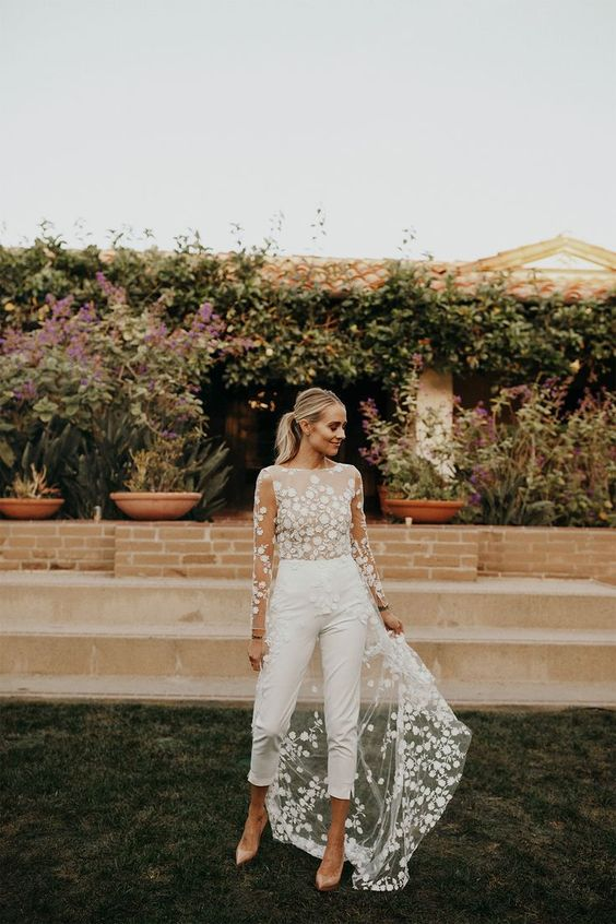 32 a refined modern wedding reception jumpsuit with cropped pants, a floral applique bodice and a long train for a whimsy touch