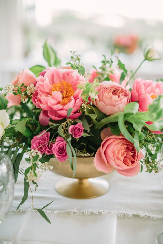 an amazing wedding centerpiece with greenery, pink roses and coral peonies with much texture is adorable for a bold wedding