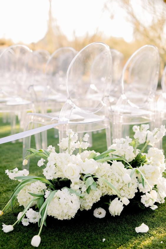 modern lux wedding ceremony space decor done with white blooms and ghost chairs is simple and very chic