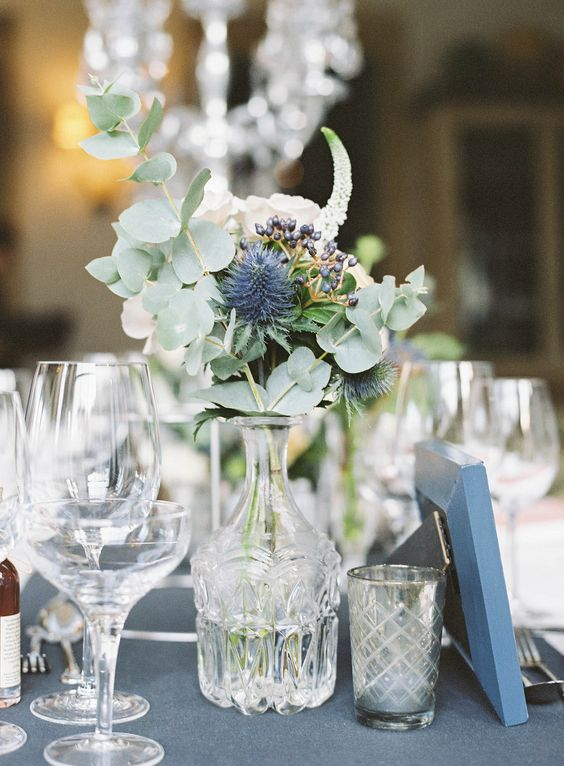 a refined wedding centerpiece of a crystal vase, white roses, thistles, berries and eucalyptus is a very beautiful idea