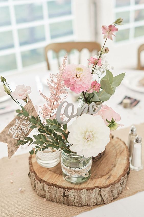 a rustic cluster wedding centerpiece of a wood slice, jars with pink and white blooms, greenery and pink astilbe, a table number and a burlap mark