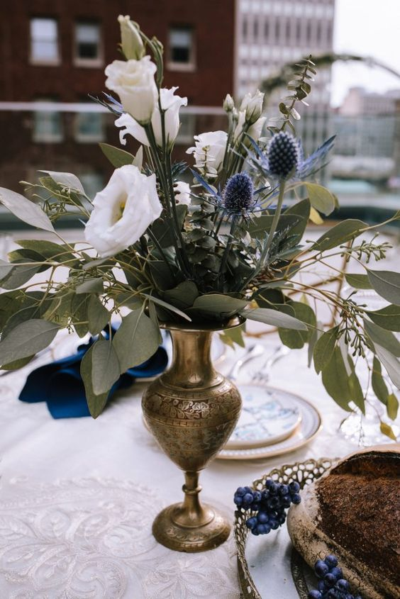 a refined wedding centerpiece of white roses, eucalyptus and thistles is a fabulous wedding decor idea
