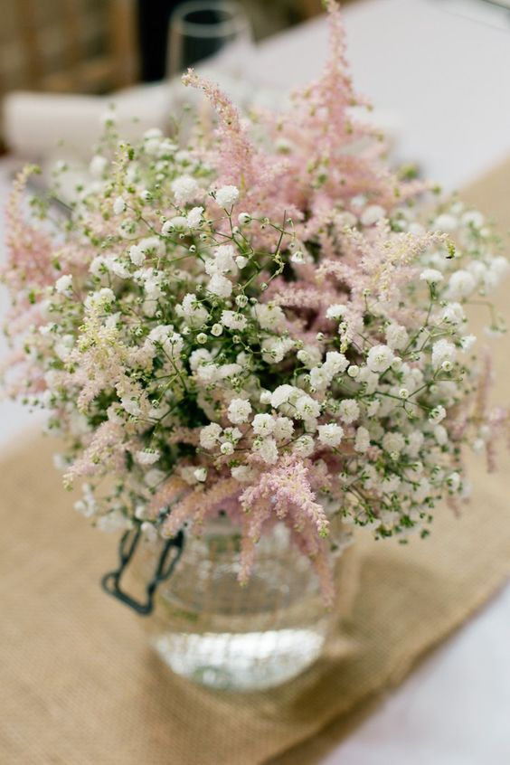 a simple and cool rustic wedding centerpiece of baby's breath and pink astilbe is a lovely idea that you can easily DIY