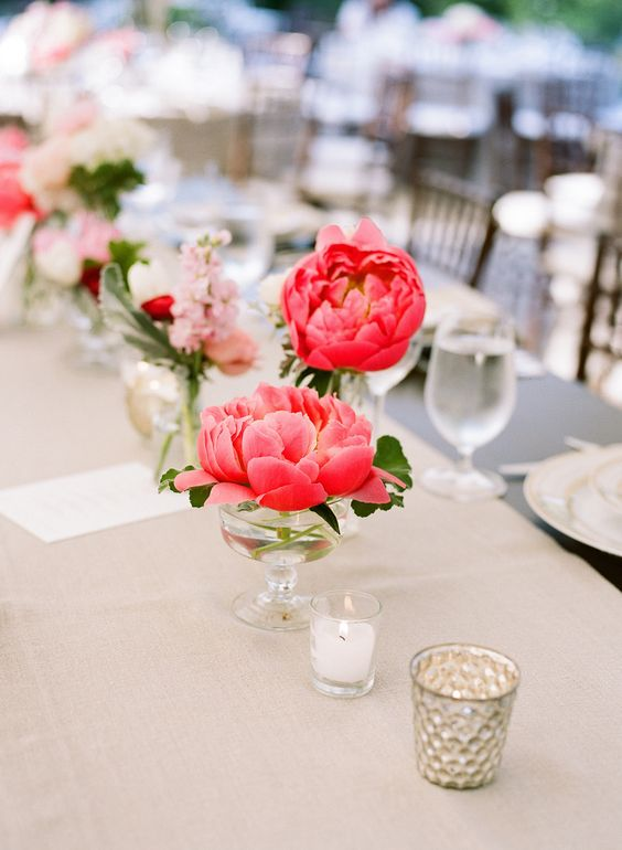 glasses with coral peonies along the table form a natural wedding table runner and add a touch of color to the space