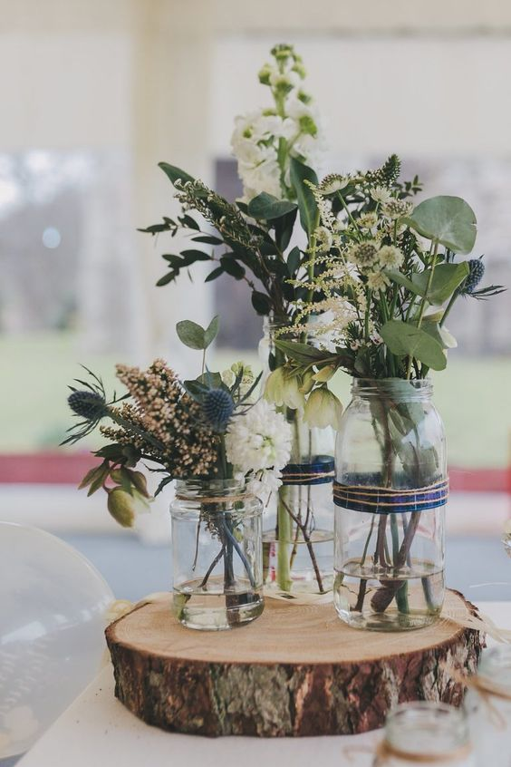 a rustic cluster wedding centerpiece of a wood slice, jars, neutral and blush blooms, greenery and thistles is wow