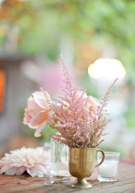 a simple yet glam wedding centerpiece of a brass cup and blush roses and astilbe is a lovely idea to try