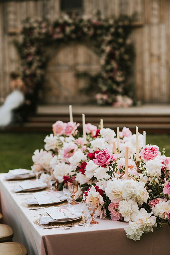 very lush and beautiful wedding table decor with white, pink and burgundy peonies and tall blush candles is amazing