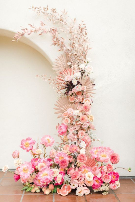 a breathtaking wedding altar with blush foliage and fronds, bold pink peonies and hot pink ones plus fruit is wow