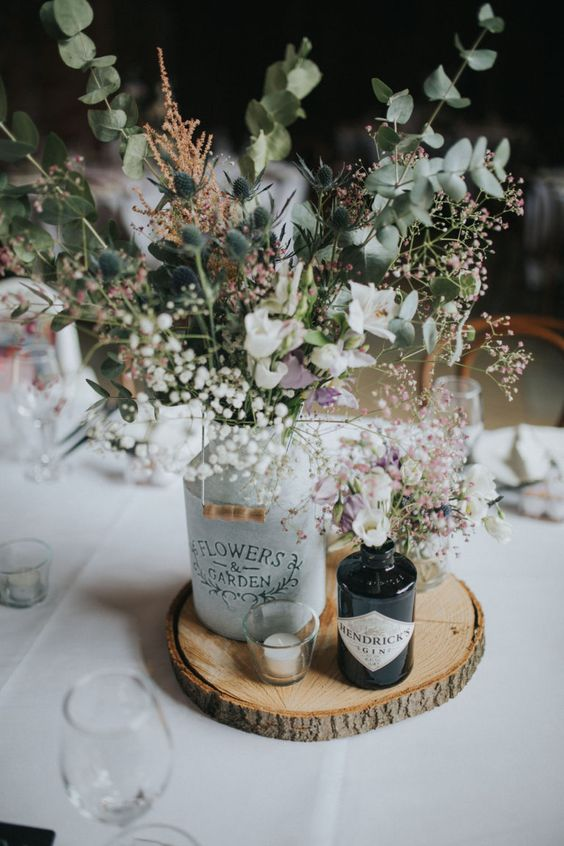 a rustic wedding centerpiece of a wood slice, bottles with white blooms, thistles and greenery and a single candle is wow