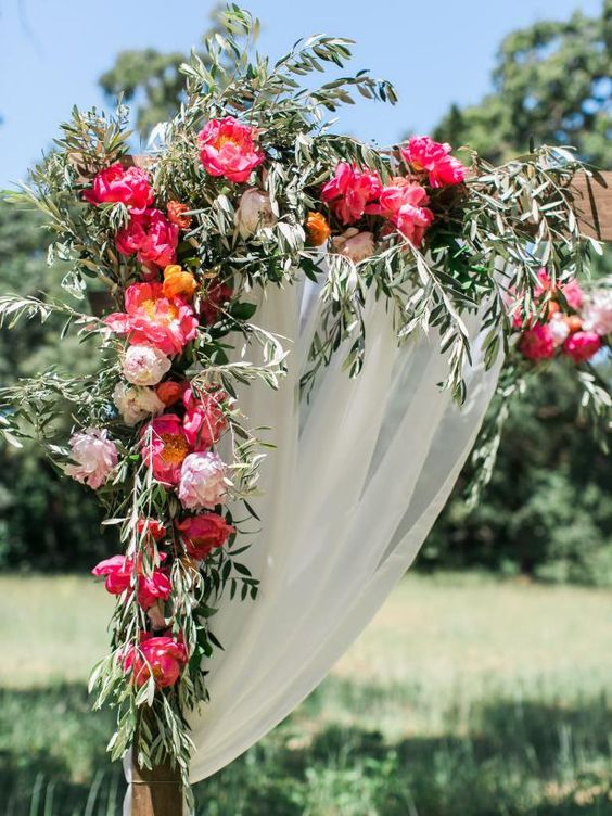 a bright wedding arch decorated with light pink and fuchsia peonies and olive branches for a colorful summer wedding