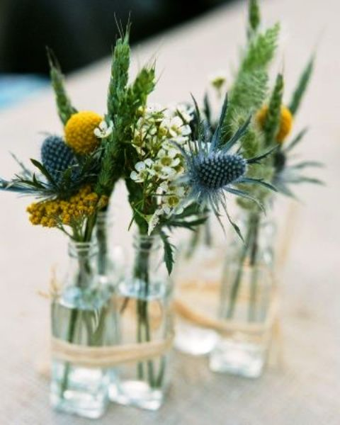 a simple rustic cluster wedding centerpiece of bottles, thistles, billy balls, white blooms and green spikes for a rustic wedding