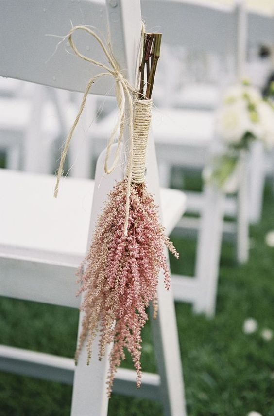an aisle chair decorated with pink asitlbe wrapped with twine is a very cool and fresh idea that won't break the bank
