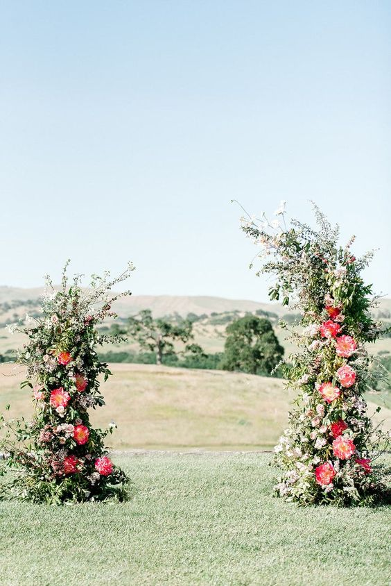 a pretty wedding altar with greenery and bright peonies is a bold modenr solution for any colorful wedding