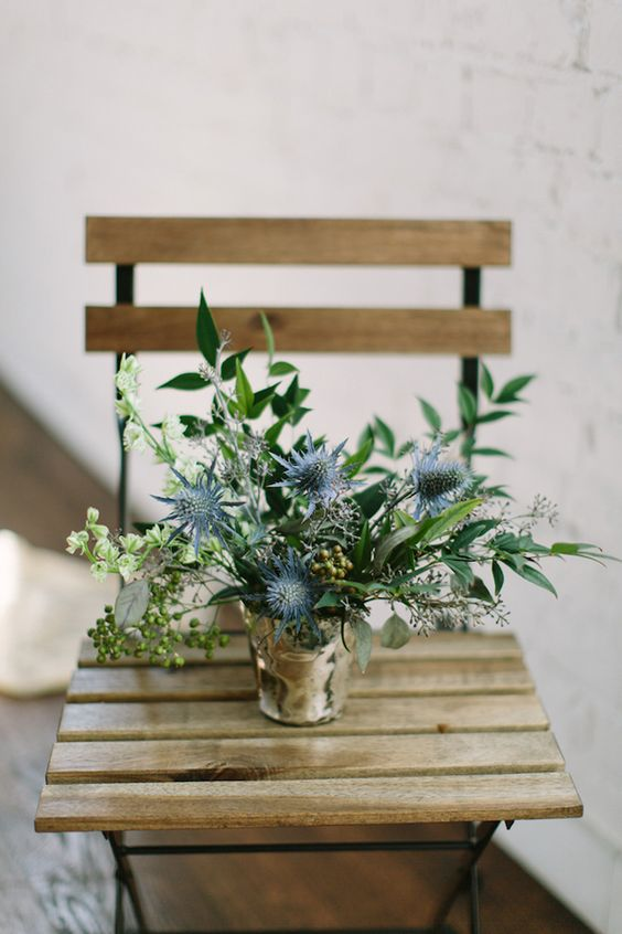 a stylish and easy wedding centerpiece of a polished bucket, thistles, greenery, berries and some white blooms is amazing