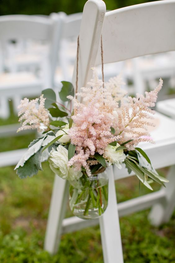 an aisle chair decorated with pink astilbe, white ranunculus and greenery is a pretty idea with a tender feel