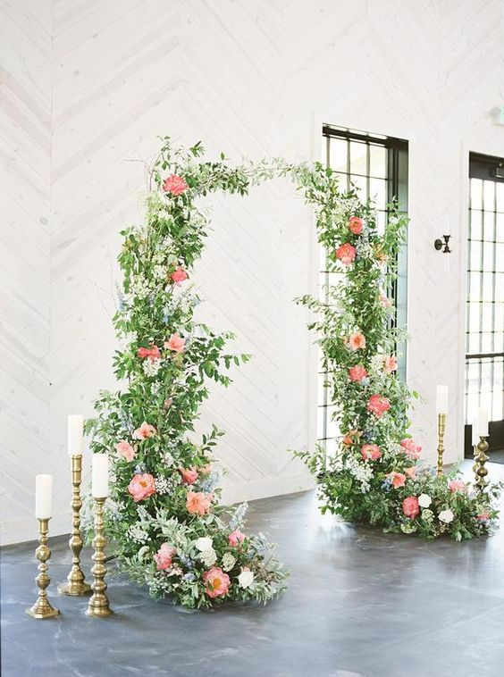 39 a refined wedding arch with greenery, pink peonies, blue and white blooms and candles around will fit a refined and chic wedding