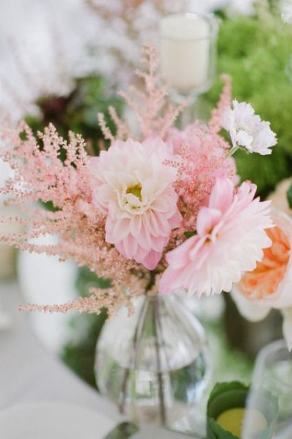 an ethereal spring wedding centerpiece of pink blooms and astilbe and a clear vase is a lovely and easy to realize idea