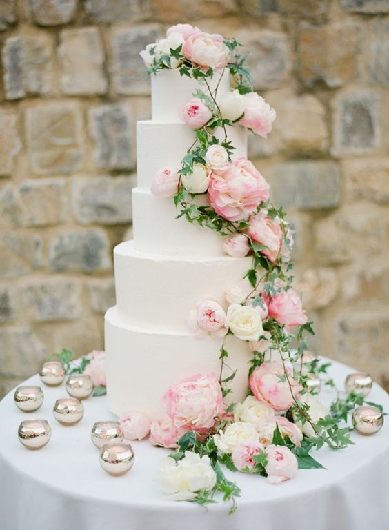 a large white wedding cake with climbing greenery, white and light pink peonies is an amazing idea