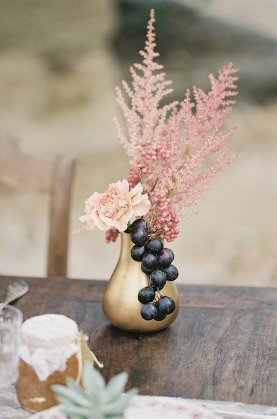 an exquisite fall wedding centerpiece of a gilded vase, a blush carnation and berries plus pink astilbe looks veyr decadent