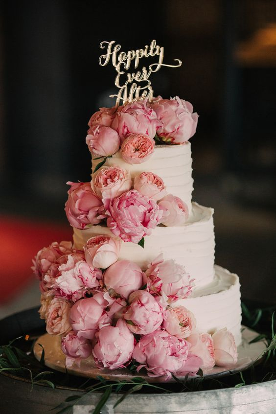 a white textural wedding cake topped with light pink peonies and with a gold calligraphy topper is amazing and romantic