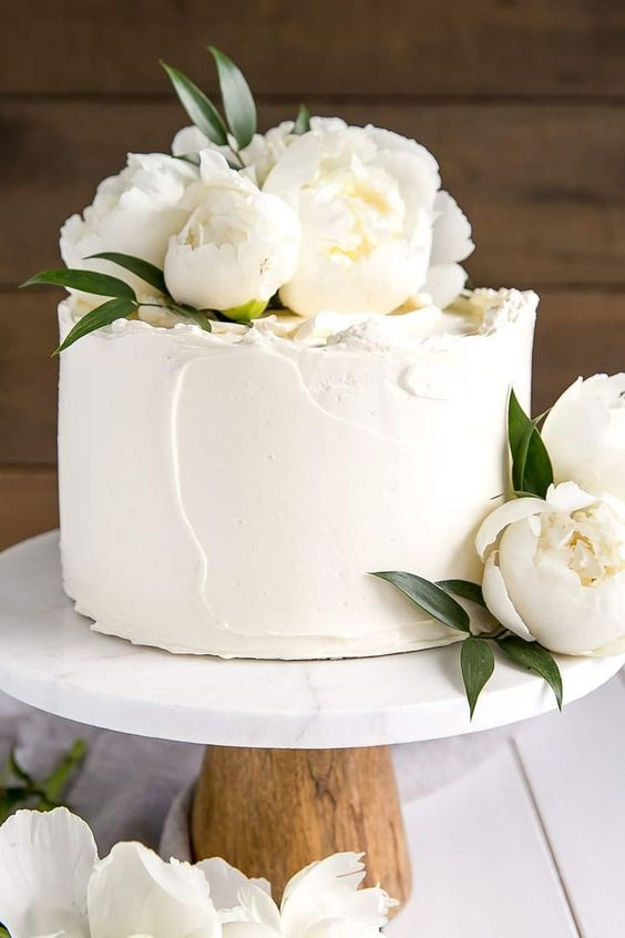 an elegant white textural wedding cake topped with white peonies and leaves is a gorgeous idea to rock