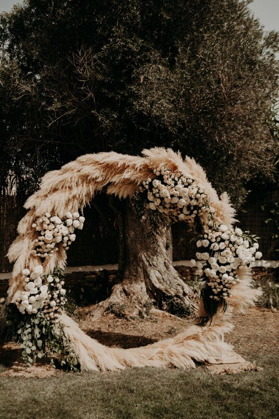 a beautiful boho round wedding arch covered with pampas grass, greenery and lush white blooms is wow