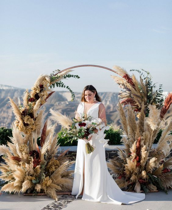 a beautiful boho round wedding arch with pampas grass and greenery and dried hydrangeas is a very lovely idea