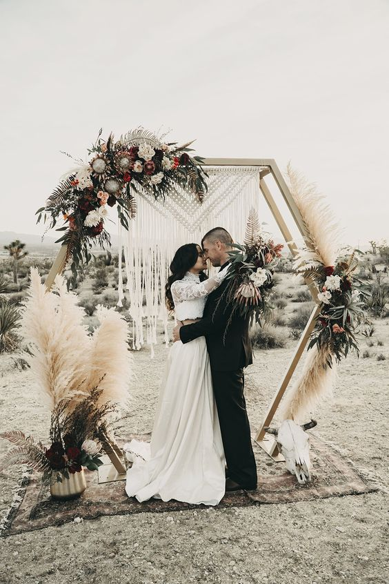 a boho hex wedding arch  with greenery, pink, white and burgundy blooms, pampas grass and other grasses and macrame
