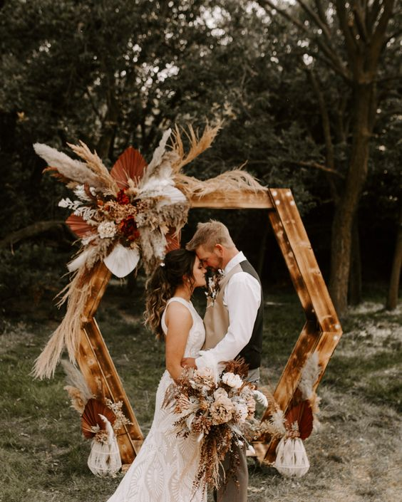 a boho hexagon wedding arch decorated with bold blooms, colorful fronds and grasses and arrangement on the ground