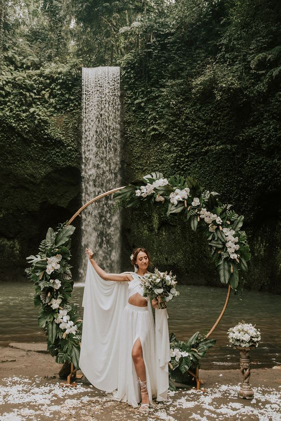 a boho tropical wedding arch decorated with fronds, white rochids and leaves is an amazing idea