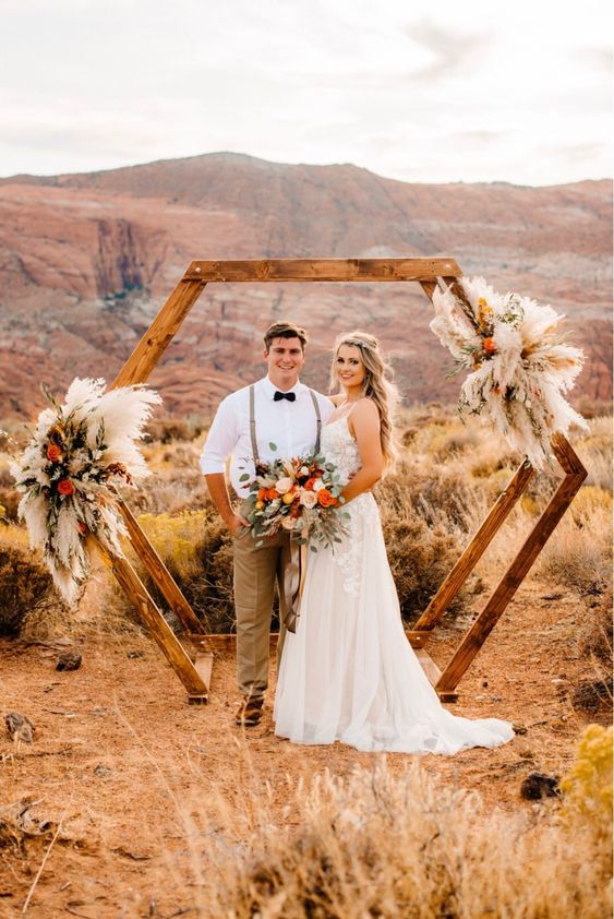 a bold boho hexagon wedding arch with pampas grass, white and red flowers is a lovely and bright idea to rock