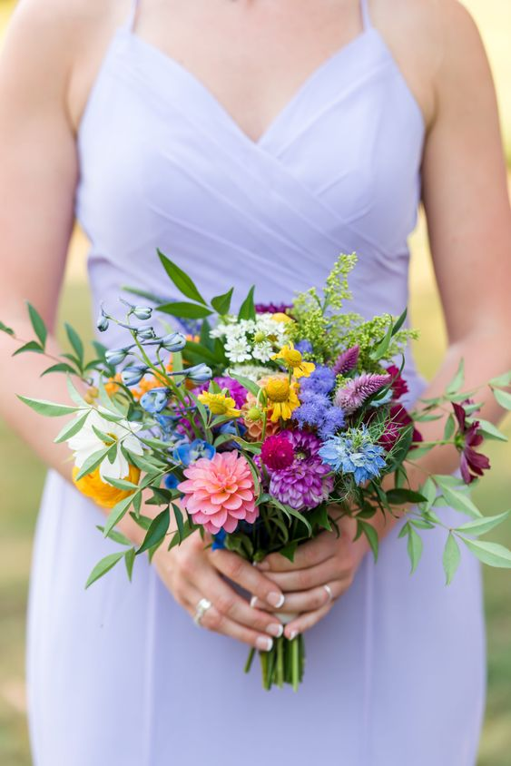 a bold bridesmaid wedding bouquet with purple, fuchsia, pink, yellow and blue blooms and greenery is pure fun
