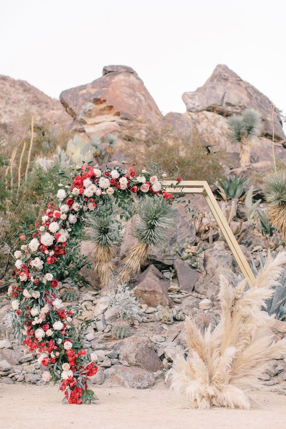 a bold hexagon wedding arch with pampas grass, greenery, blush, white and red flowers for a boho wedding