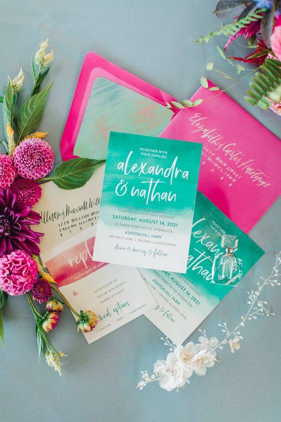 a bold mermaid weddig invitation suite done in turquoise and hot pink, with creative lettering and cool gold touches
