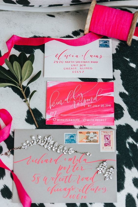 a bold modern wedding invitation suite with a grey envelope, hot pink invites and bright calligraphy is fun