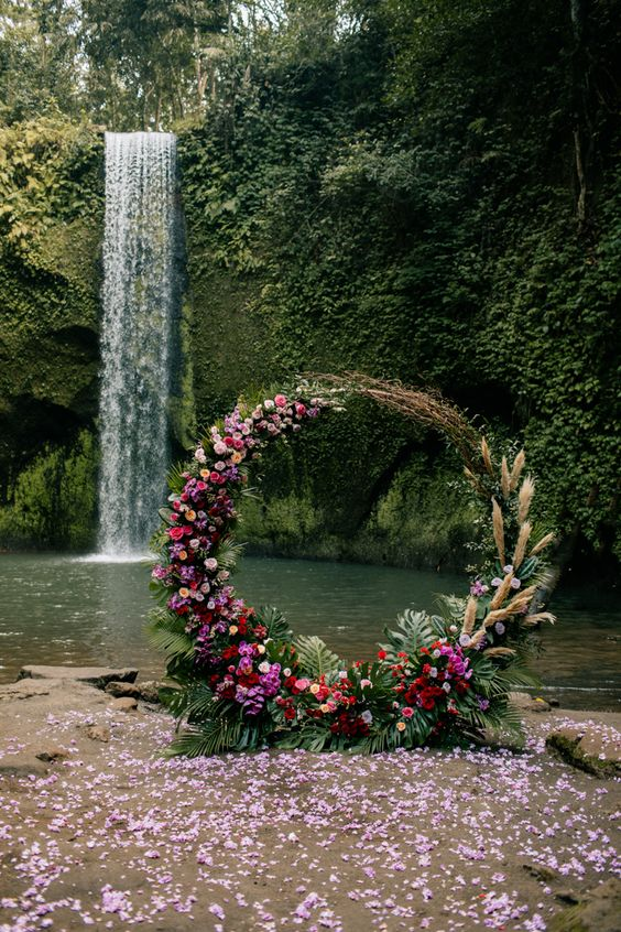 a bold tropical wedding arch with fronds, pampas grass, hot pink, red and blush blooms is a pretty idea for a boho wedding
