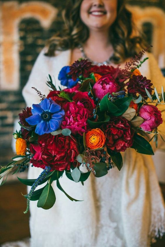 a bold wedding bouquet with fuchsia, red, blue, yellow flowers, privet berries and foliage for a bright fall wedding