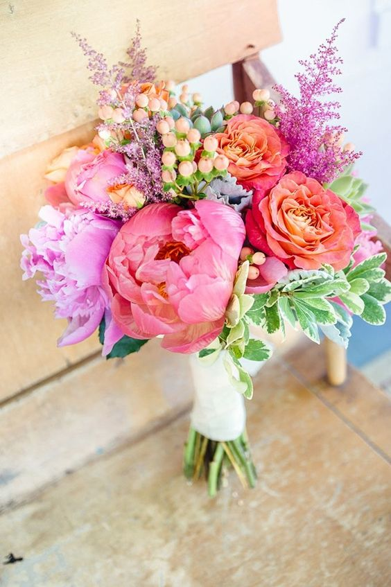 a bold wedding bouquet with pink, purple, red and yellow blooms, berries, foliage is a lovely idea for a summer wedding