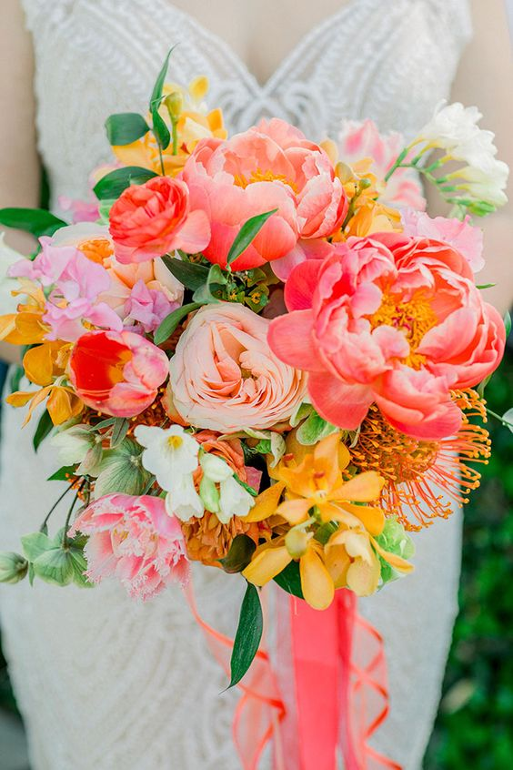 a bold wedding bouquet with red, pink, blush and yellow blooms, some greenery and coral ribbons for a bolder look