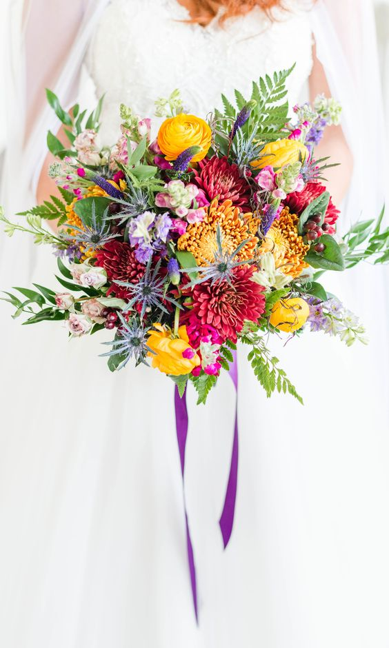 a bold wedding bouquet with yellow, burgundy, purple blooms, greenery, astilbe and purple ribbons is fun