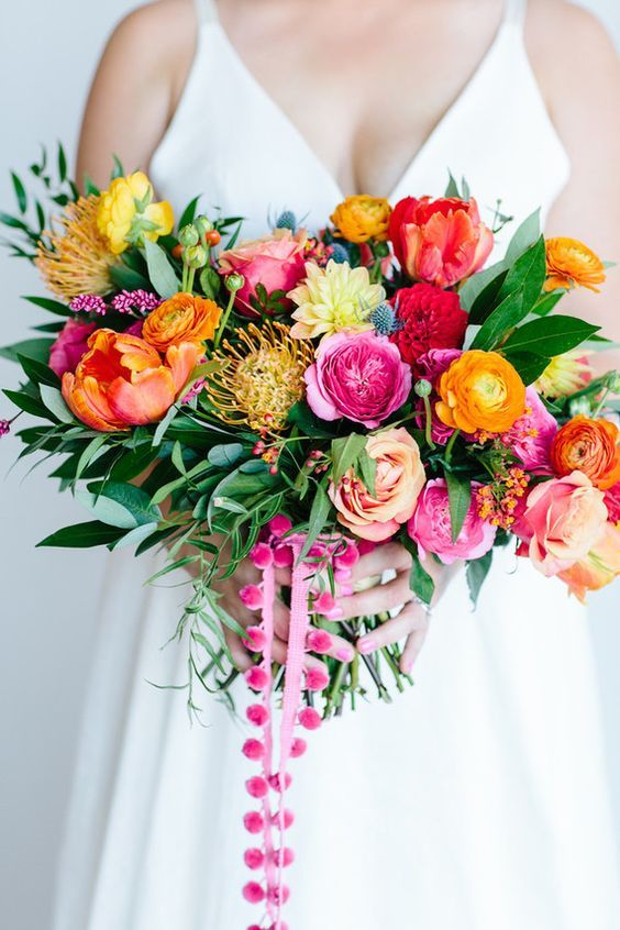 a bold wedding bouquet with yellow, orange, pink, blush, yellow blooms, pincushion proteas, greenery and pink pompoms