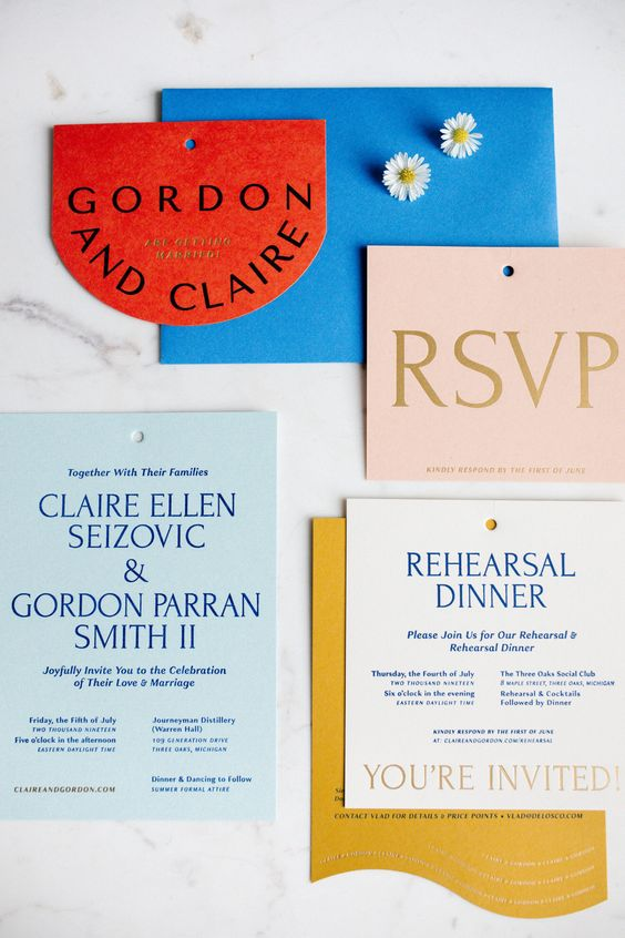 a bold wedding invitation suite in electric blue, light blue, blush, red and mustard, with catchy shapes and lines
