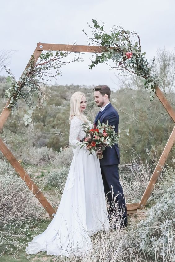 a breezy wedding arch with greenery branches and a couple of pink blooms for an elegant nature-loving wedding