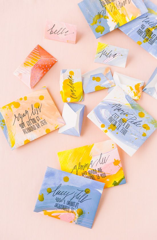 a bright and fun wedding invitation suite in yellow, peachy, blues and splashes of paint and black calligraphy